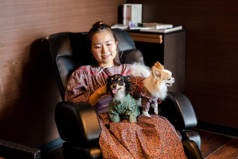 マッサージチェアに座る中原さんと愛犬