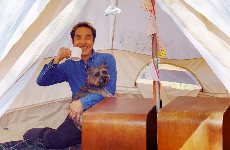 ティピーの中で愛犬と一緒に過ごすオーナー