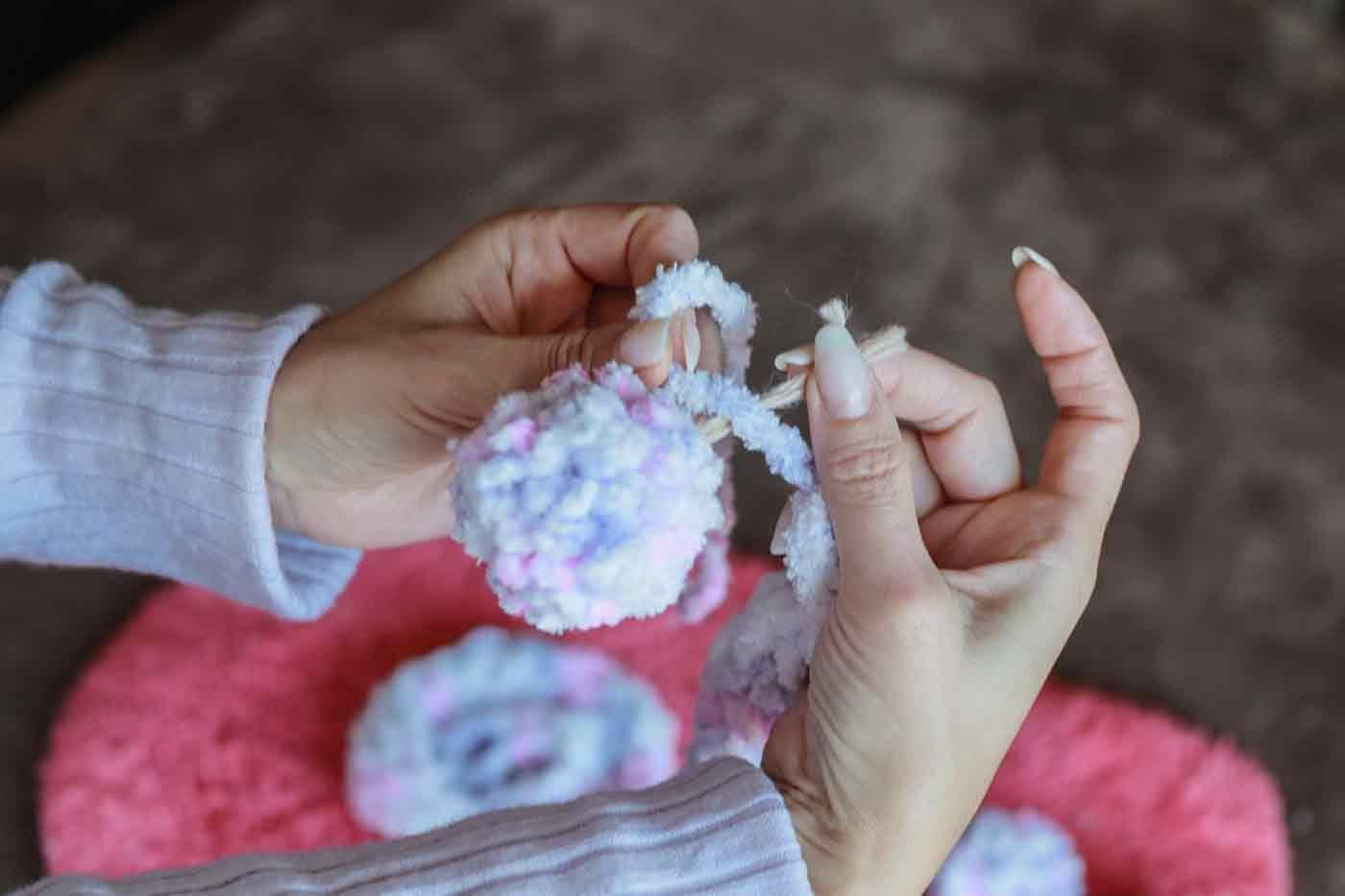 愛犬用指編み マフラーにポンポンを結びつける
