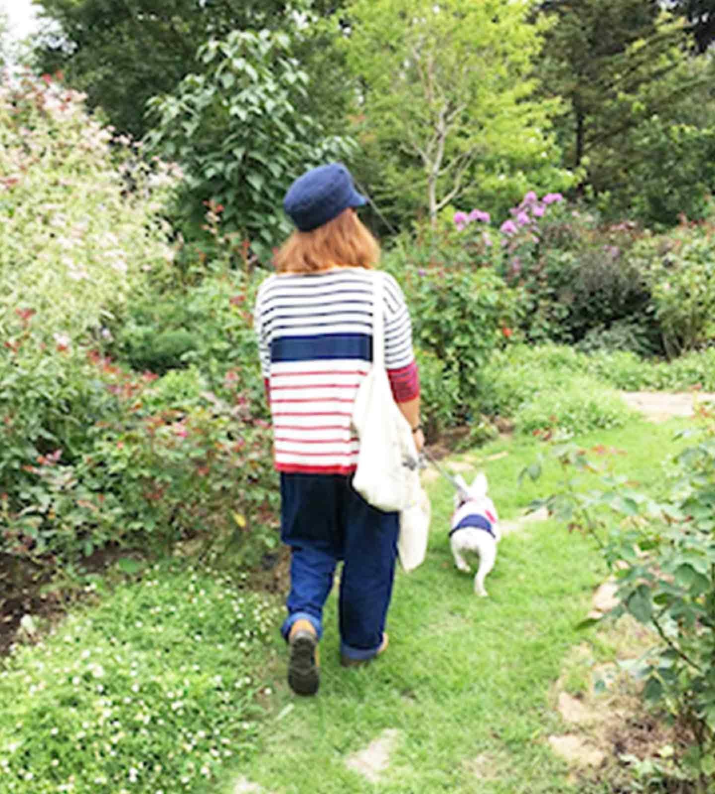 緑に囲まれた庭を散歩する犬と飼い主
