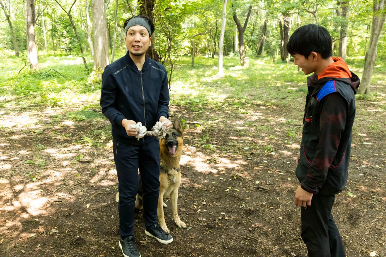かじりんボーンを手に持つ犬が大好きなライターの竹内と訓練士の稲留さんとジャーマン・シェパードの警察犬パクくん
